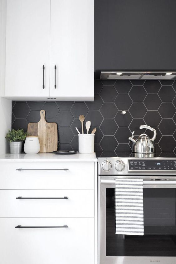 a minimalist white kitchen with a matte black hexagon tile backsplash, which is accented with white grout