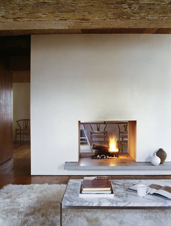 a modern white double-sided fireplace with a concrete stand is a cozying up and chic idea for a modern space