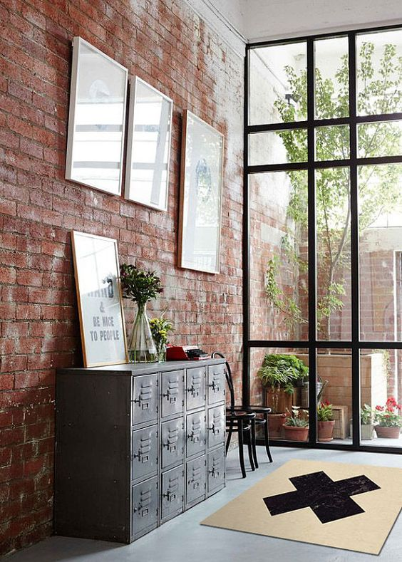 a red brick wall and a vintage metal cainet make the spac industrial and give it a vintage feel at the same time