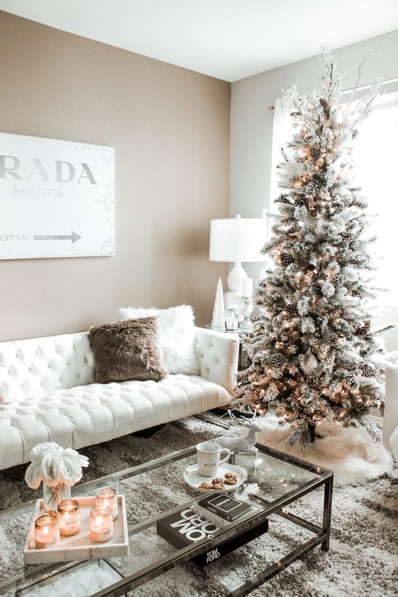 a snowy Christmas tree with pinecones and lights and some white branches on top, candles and fluffy pillows