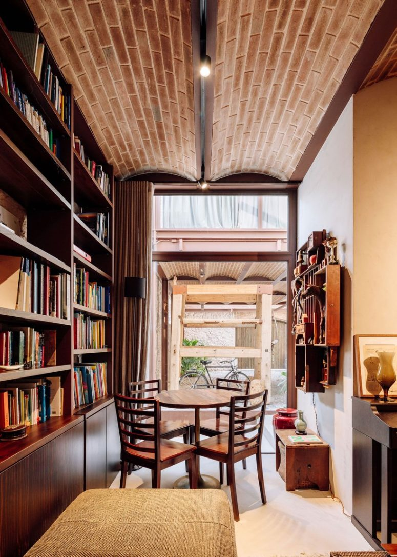 Here's a reading nook paired with a breakfast one, with large bookcases, a comfy daybed and a dining set