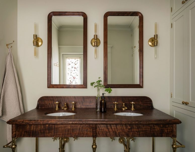 The bathroom features a dark walnut wooden vanity with brass touches and a duo of mirrors