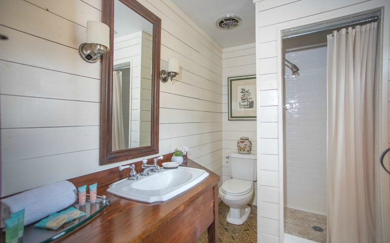 The bathroom is done with white shiplap and tiles, a walk-in shower and a vanity of rich stained wood