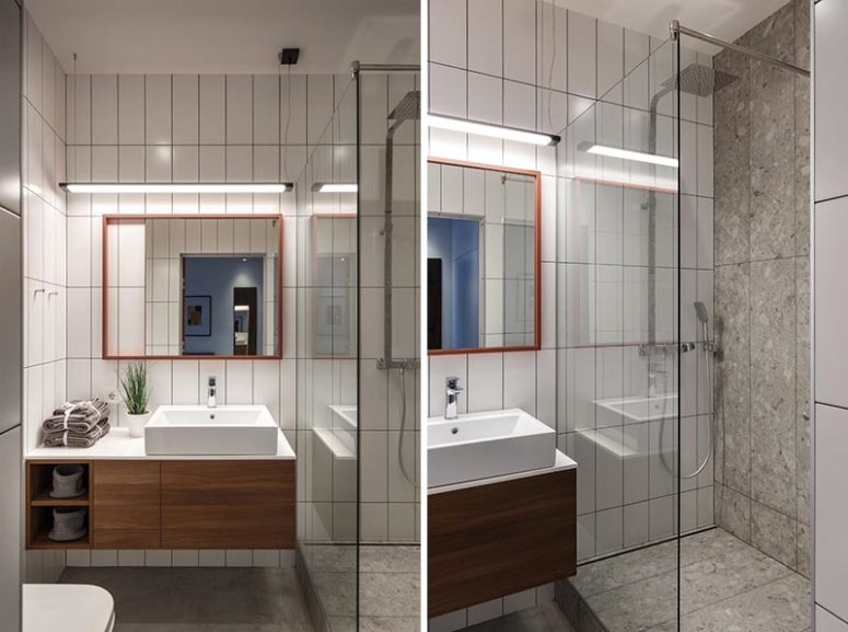 The bathroom is small and simple, with white tiles and a floating vanity plus a shower space in the corner