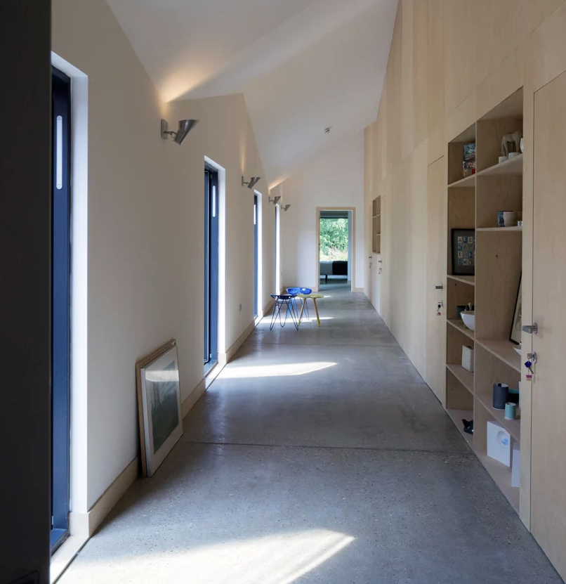 The hallway is long and light filled, with a whole wall taken by plywood storage furniture