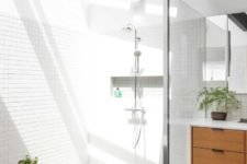 08 The shower space shows off a skylight, the white tiles reflect it maing this nook sunny