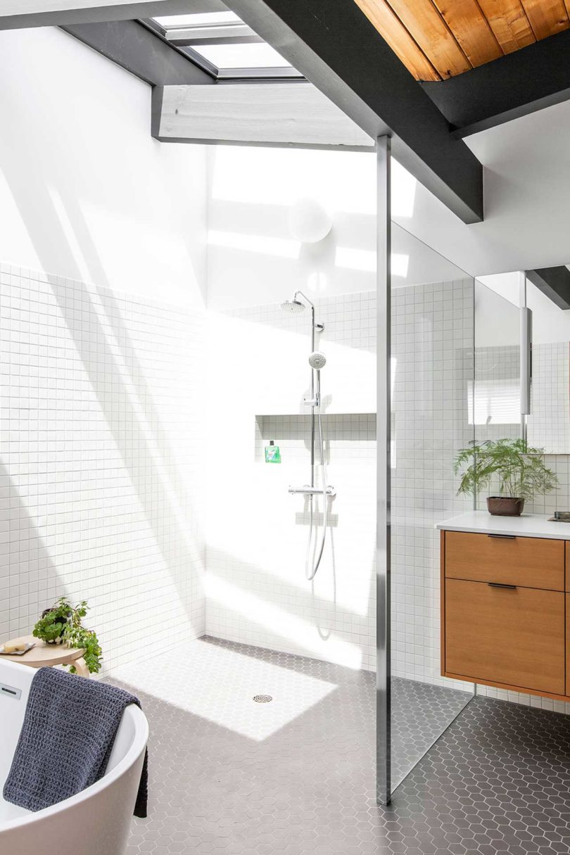 The shower space shows off a skylight, the white tiles reflect it maing this nook sunny