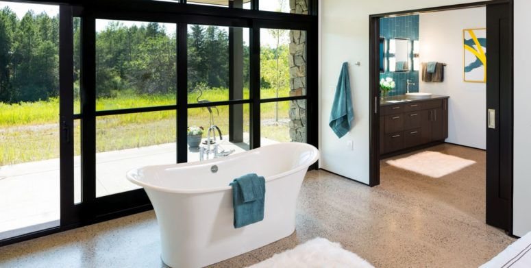 There's a free-standing tub by a glazed wall, with an advantage of the scenery