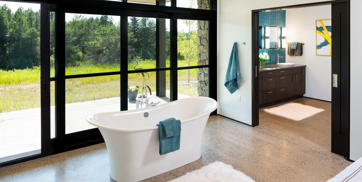 There's a free standing tub by a glazed wall, with an advantage of the scenery