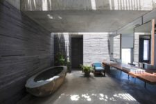 08 There's also an indoor-outdoor bathroom with a carved stone tub and a large floating vanity with mirrors