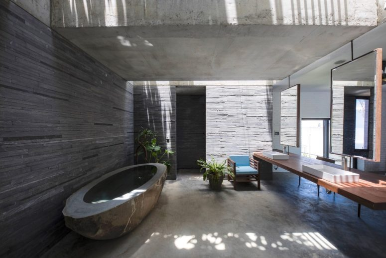 There's also an indoor-outdoor bathroom with a carved stone tub and a large floating vanity with mirrors