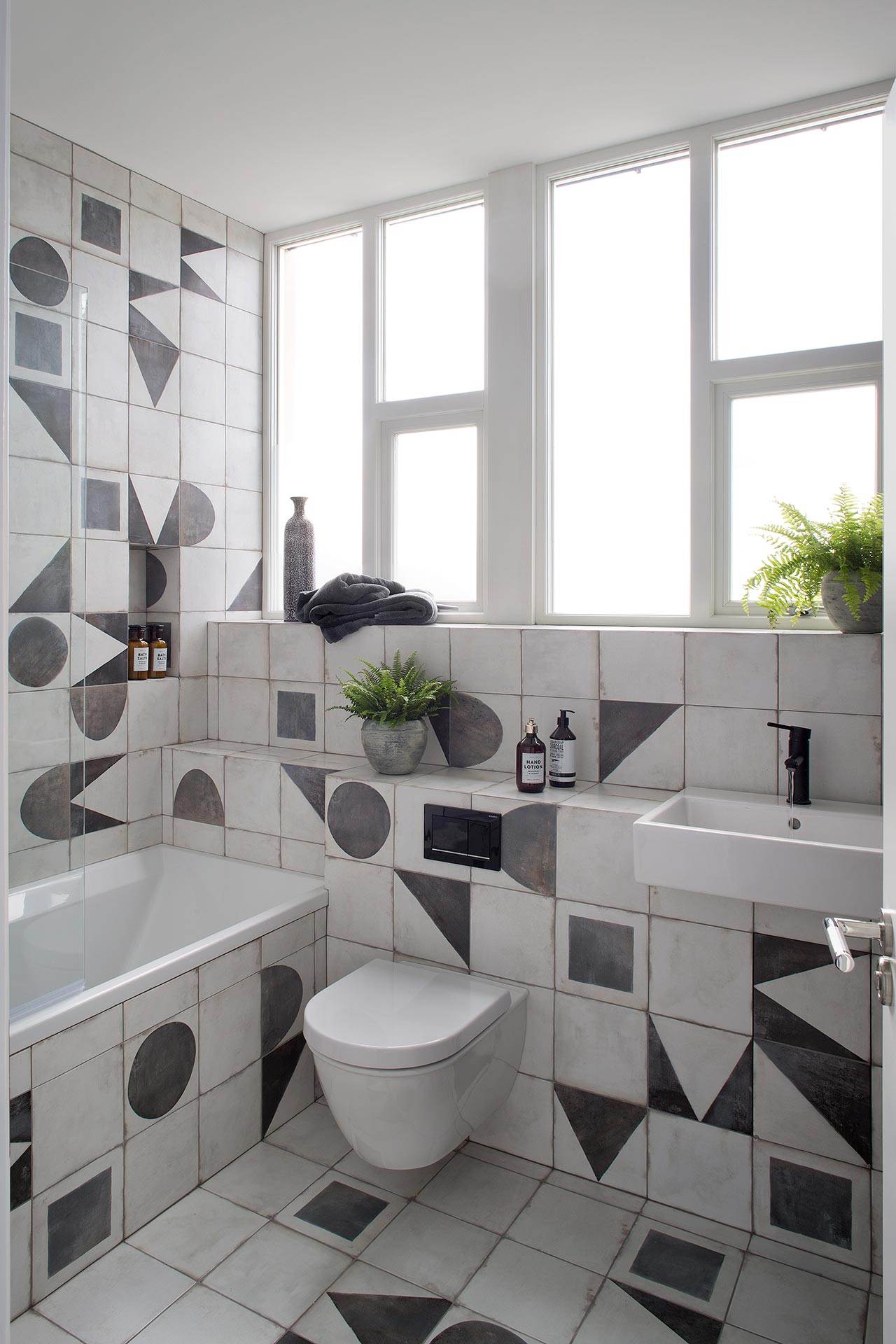 This is a black and white bathroom with geometric tiles and a bathtub, there's a window with frosted glass