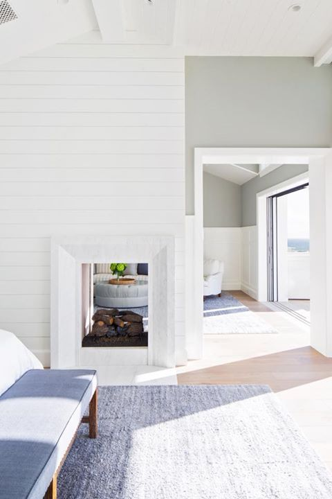 a coastal home with a double-sided fireplace that is clad with shiplap and brings coziness to the neutral spaces