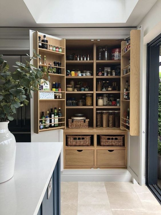 a large built-in pantry with neutral shelves, drawers and baskets feels and looks rustic