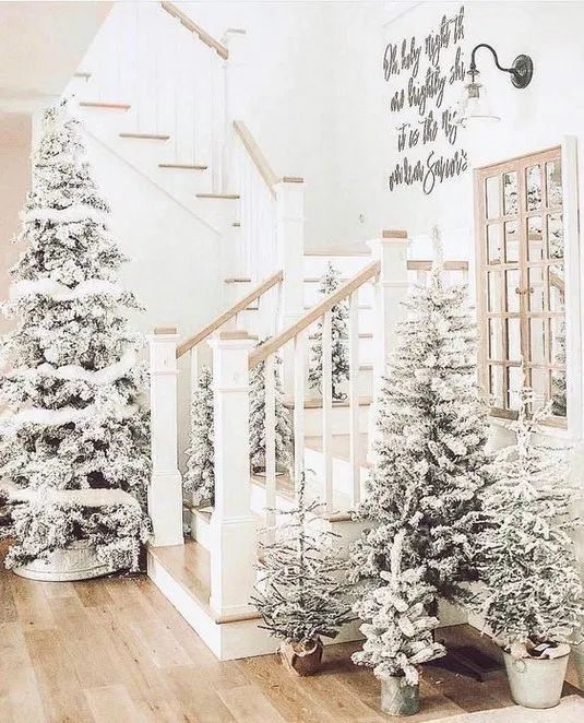 a winter entryway decorated with lots of flocked Christmas trees of various sizes with no decor is a fairy tale