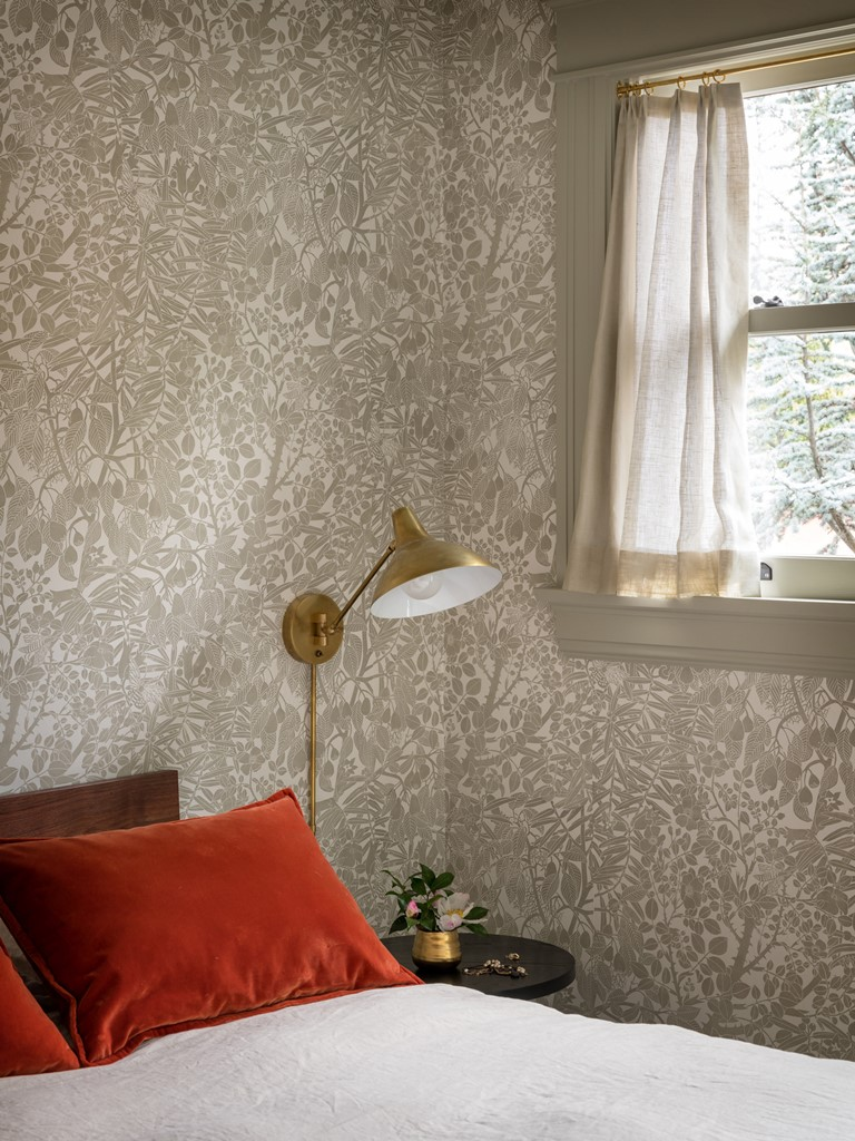 Another bedroom is done with grey printed wallpaper, rust pillows and brass touches