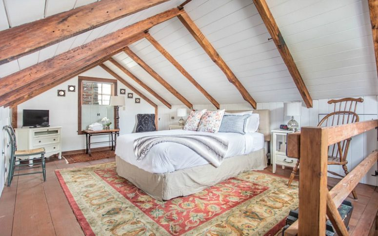 The bedroom is done with wooden beams, white shiplap, printed rugs and elegant neutral furniture