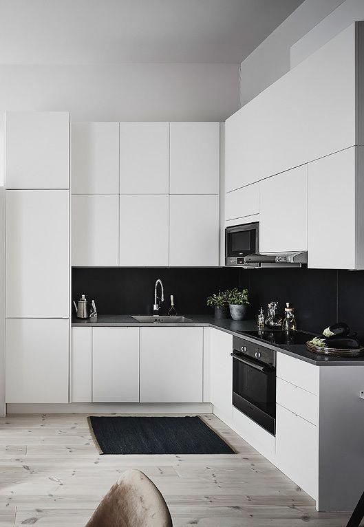 a sleek white kitchen with black large scale tile backsplash that contrasts and stands out a lot