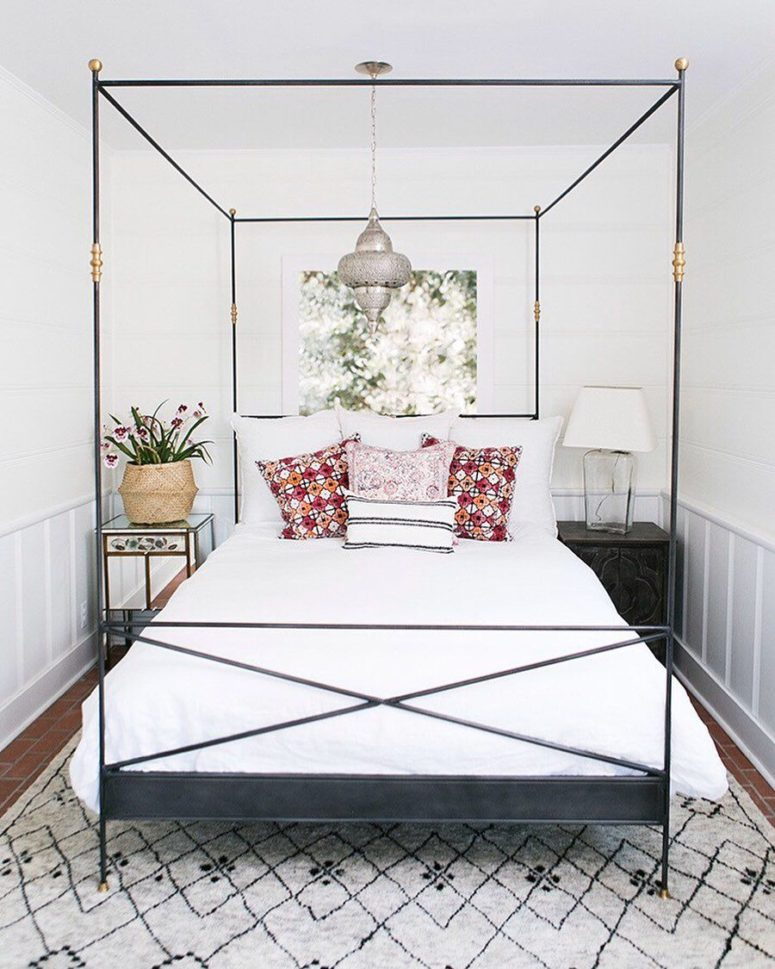 a very elegant and chic black canopy bed with gilded touches and a Moroccan pendant lamp over the bed
