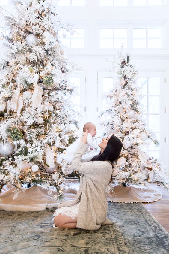 flocked Christmas trees with neutral ornaments, ribbons, berries and lights look very fairy-tale-like