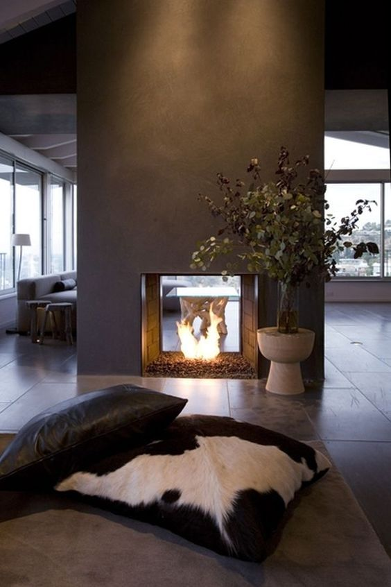 a modern double-sided fireplace done of grey concrete looks really spectacular and very chic