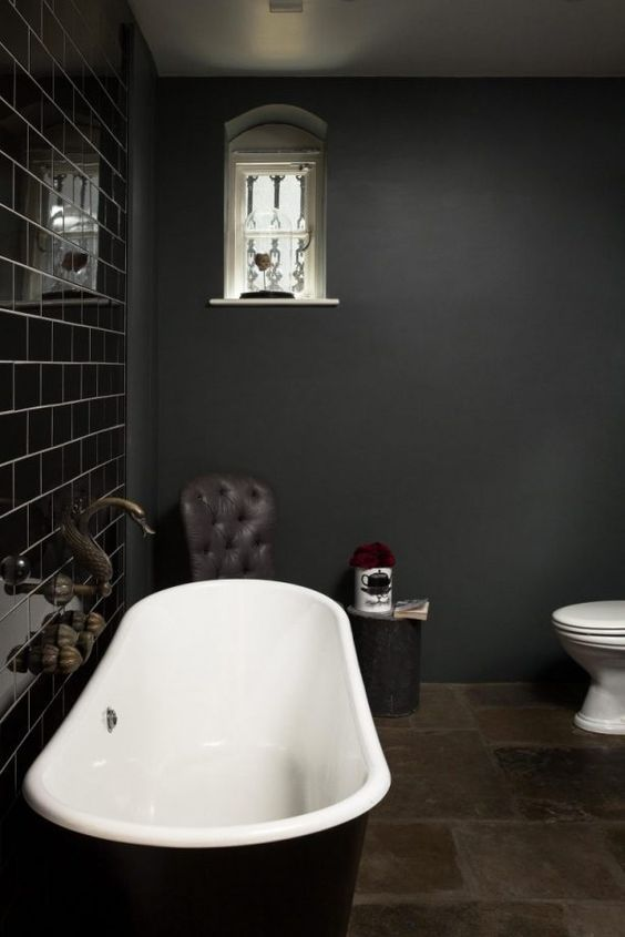 a stylish dark and moody bathroom with a shiny black tile wall and all matte everything plus a black tub