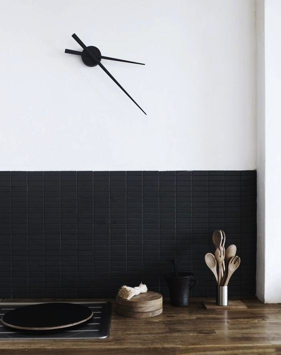 a super contemporary backsplash with matte black long and narrow tiles contrasts the light-colored butcher block
