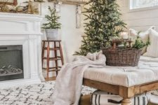10 mini Christmas tree in buckets and a Christmas tree with lights, a basket with evergreens and a neutral blanket