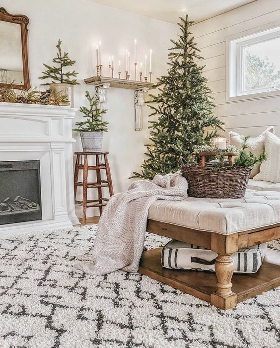 mini Christmas tree in buckets and a Christmas tree with lights, a basket with evergreens and a neutral blanket