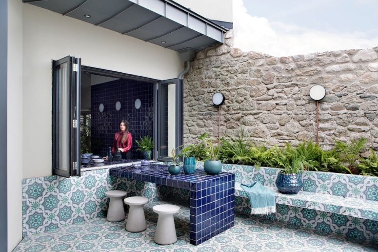 The terrace is done in Moroccan boho style, with printed tiles and lots of greenery