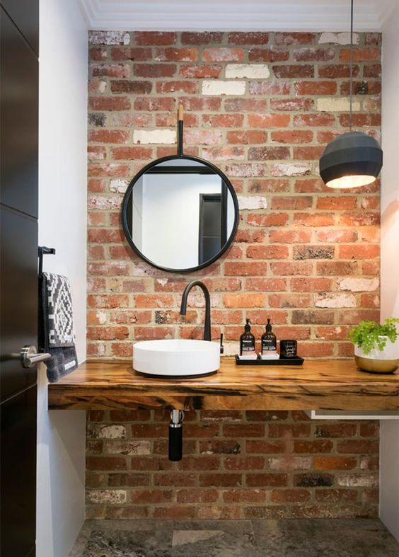 a contemporary bathroom is made cooler and more modern with a red brick wall and a felt pendant lamp
