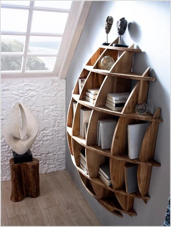 a creative semi-circular wooden shelving unit with books and sculptures is art itself