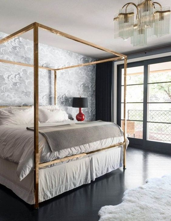 a glam brass canopy bed, an echoing chandelier and shiny black floors add chic and glam to the bedroom
