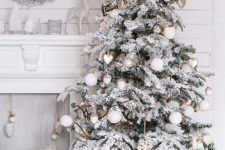 11 a neutral winter nook with a flocked Christmas tree with white ornaments, a snowy wreath on the wall, a white fireplace and pastel pillows