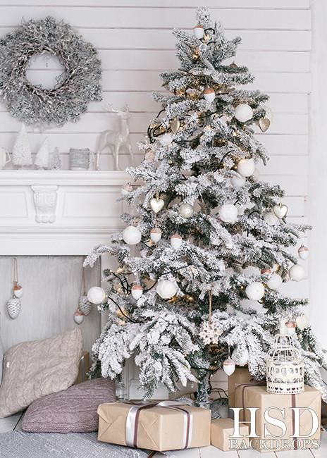 a neutral winter nook with a flocked Christmas tree with white ornaments, a snowy wreath on the wall, a white fireplace and pastel pillows