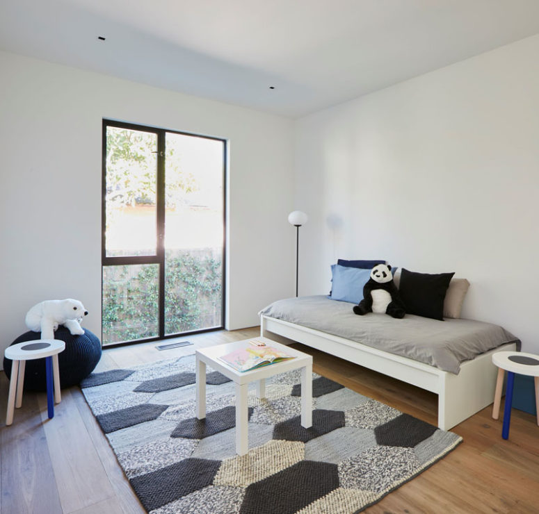 The second kid's room is also rather minimal but with a comfy rug and colorful pillows