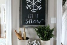 12 a chalkboard sign, a white pompom garland that imitates snowballs and some greenery and cotton in cans