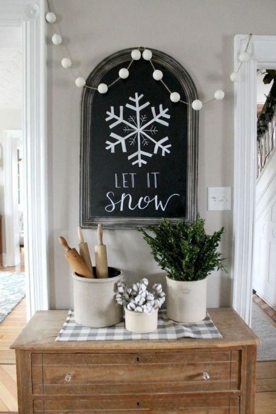a chalkboard sign, a white pompom garland that imitates snowballs and some greenery and cotton in cans