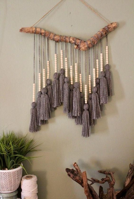 a cool boho wall hanging with large grey tassels and wooden beads and a natural branch is very bold