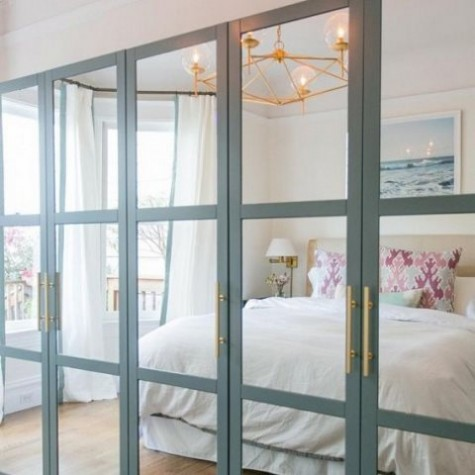 an IKEA Pax wardrobe with fully mirrored front panels with aqua frames and brass handles