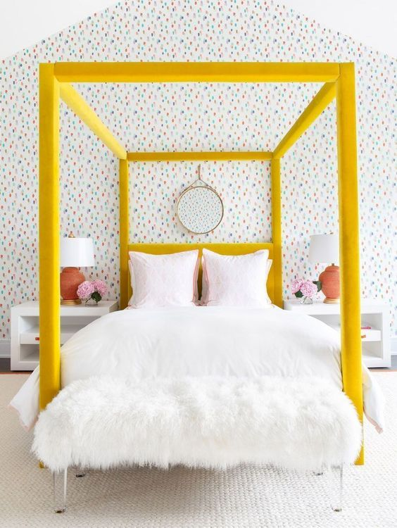 a bold yellow velvet upholstered canopy bed is a colorful statement in the bedroom that brings cheer