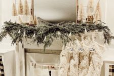 13 a cozy neutral winter fireplace with an evergreen garland, mini bottle bruch trees, knit stockings with ornaments and book pages