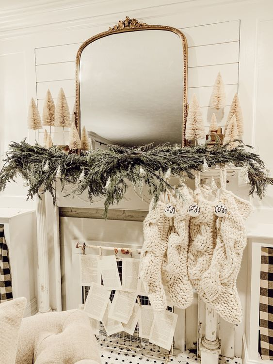 a cozy neutral winter fireplace with an evergreen garland, mini bottle bruch trees, knit stockings with ornaments and book pages