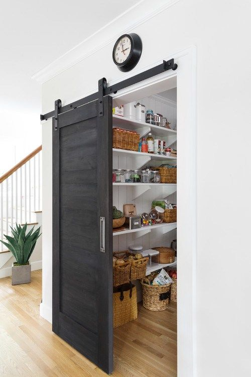 a farmhouse pantry with a dark sliding door, which doesn't take any space and makes a statement with its color