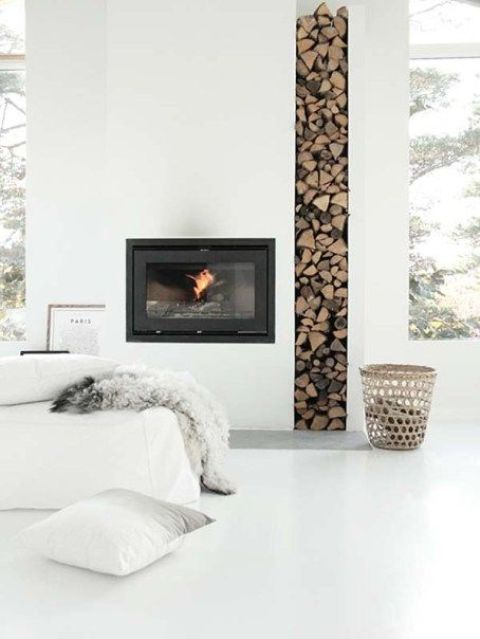a minimalist built-in fireplace with a tall and narrow firewood storage space looks very edgy