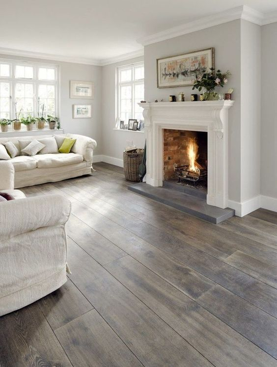 a neutral rustic living room with a grey hardwood tone floor that brings a touch of warm color and coziness