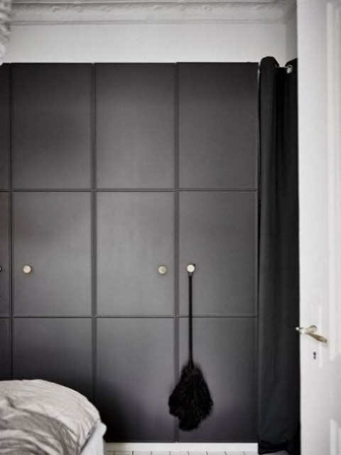 an IKEA Pax wardrobe with black molded doors and metal knobs for a minimalist space