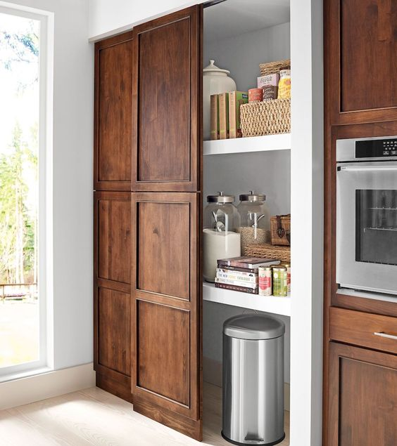 a built-in pnatry with a sliding traditional door that matches the whole kitchen design is a cool idea