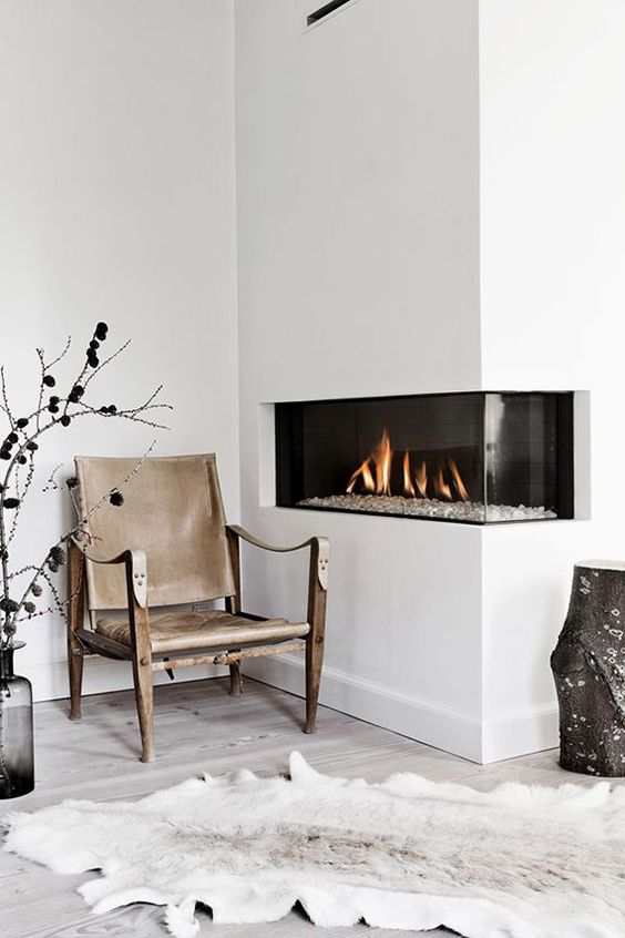 a cozy minimalist nook with a fireplace built into the corner to make the space more spectacular and see more of the fire
