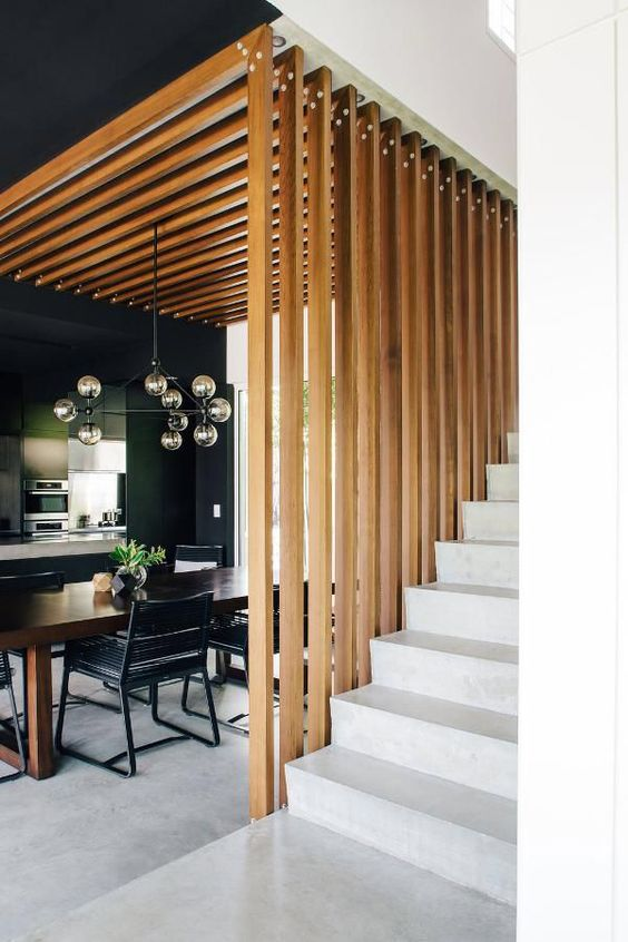 a dining space wraped in a vertical wooden plank screen on one side and from above that makes it a design feature